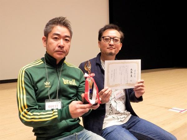グランプリの賞状・トロフィーと共に松尾プロデューサー、水落監督